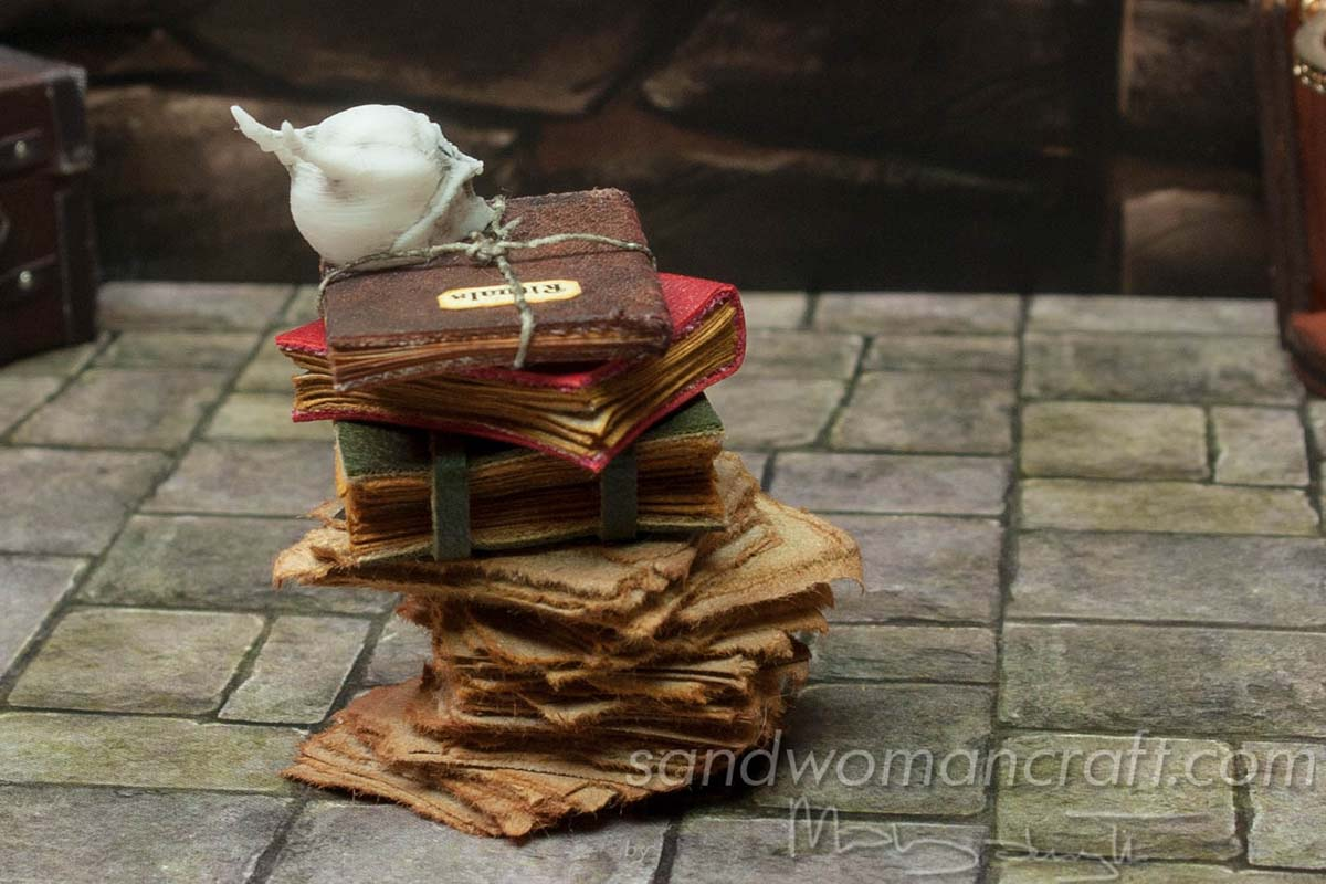 Miniature books stacked with monster skull and Rituals book