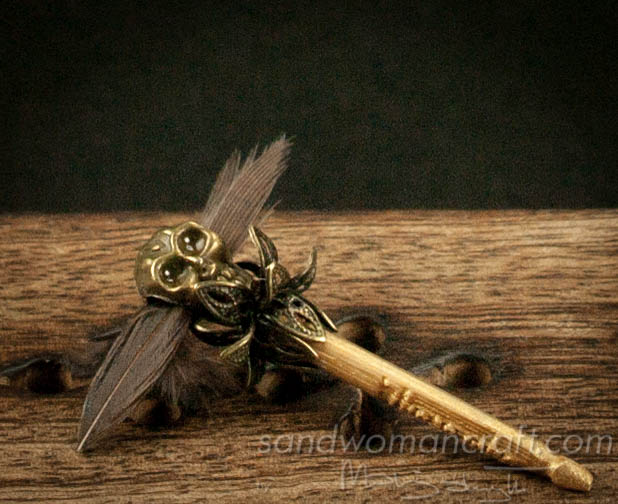 Miniature magic wand with brass skull and feathers