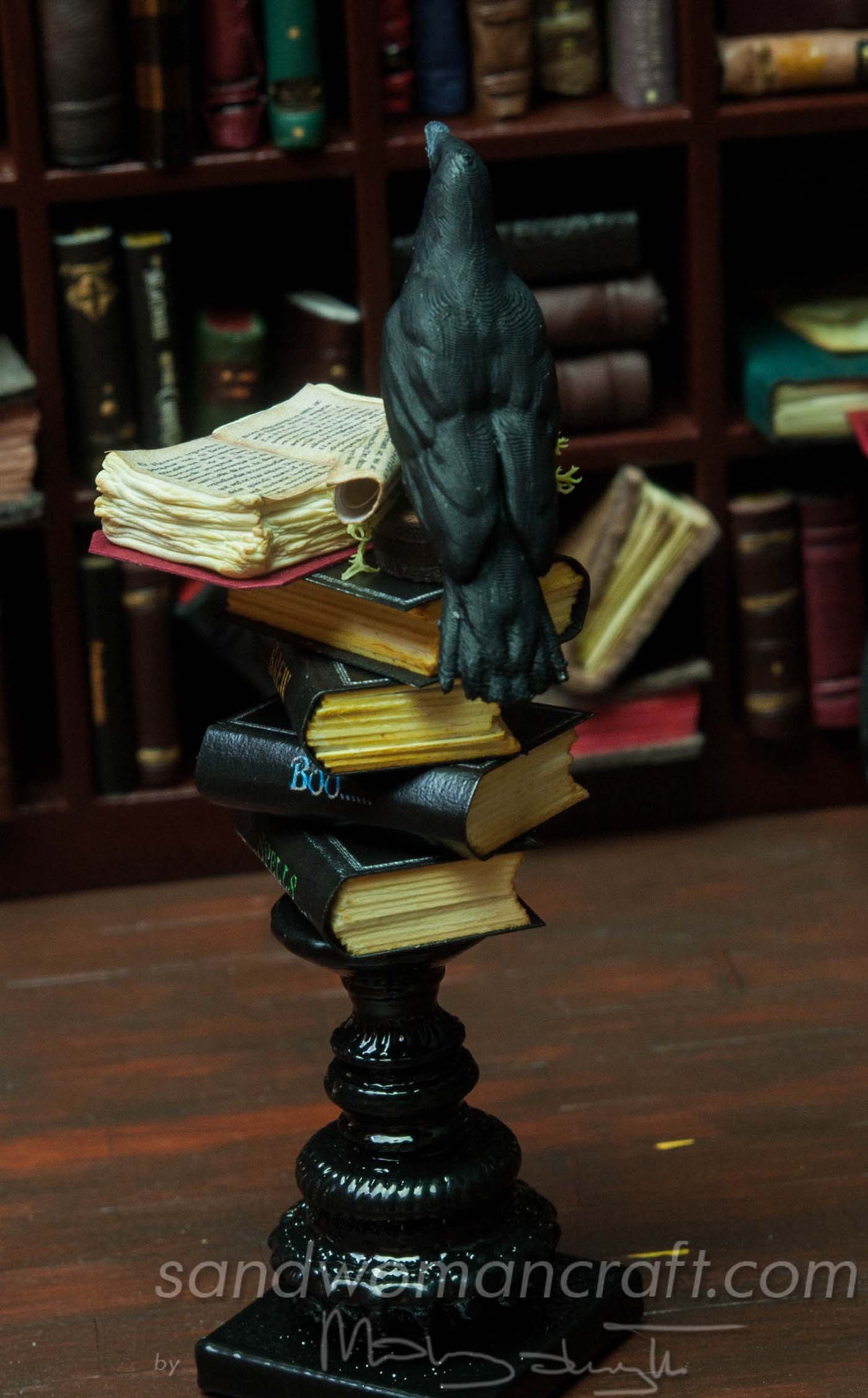 Miniature book stack with crow on black stand