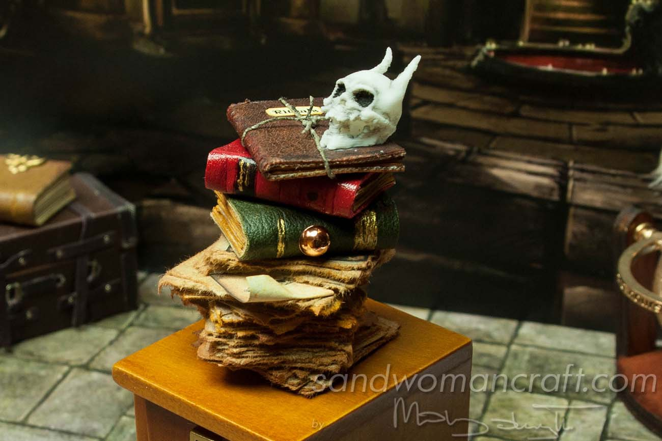 Miniature book stack with leather books and skull of monster
