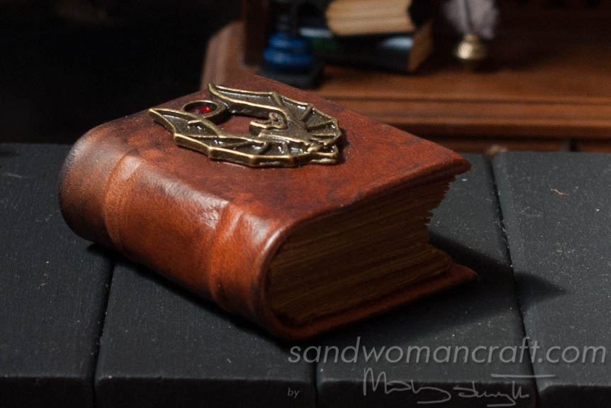 Miniature leather bound book with bat in 1:6 scale