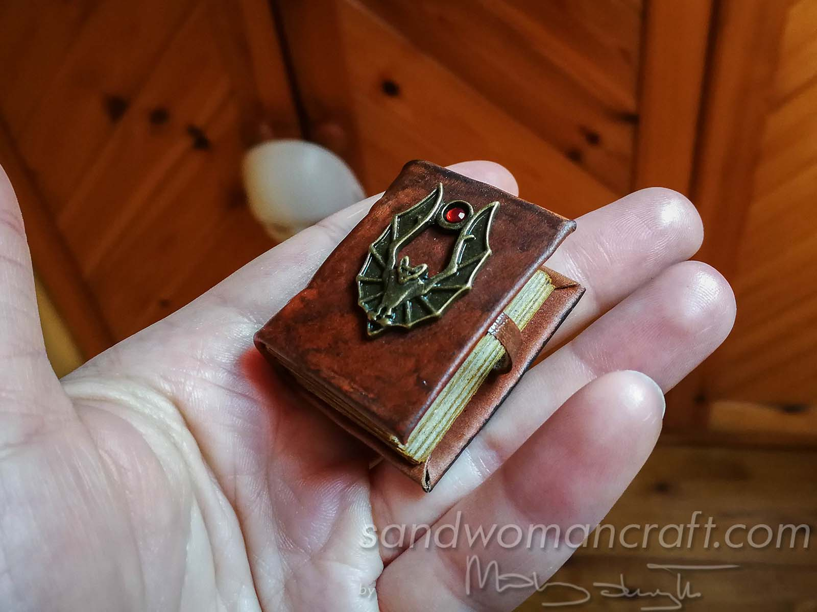 Miniature leather bound book with metal bat in 1:6 scale