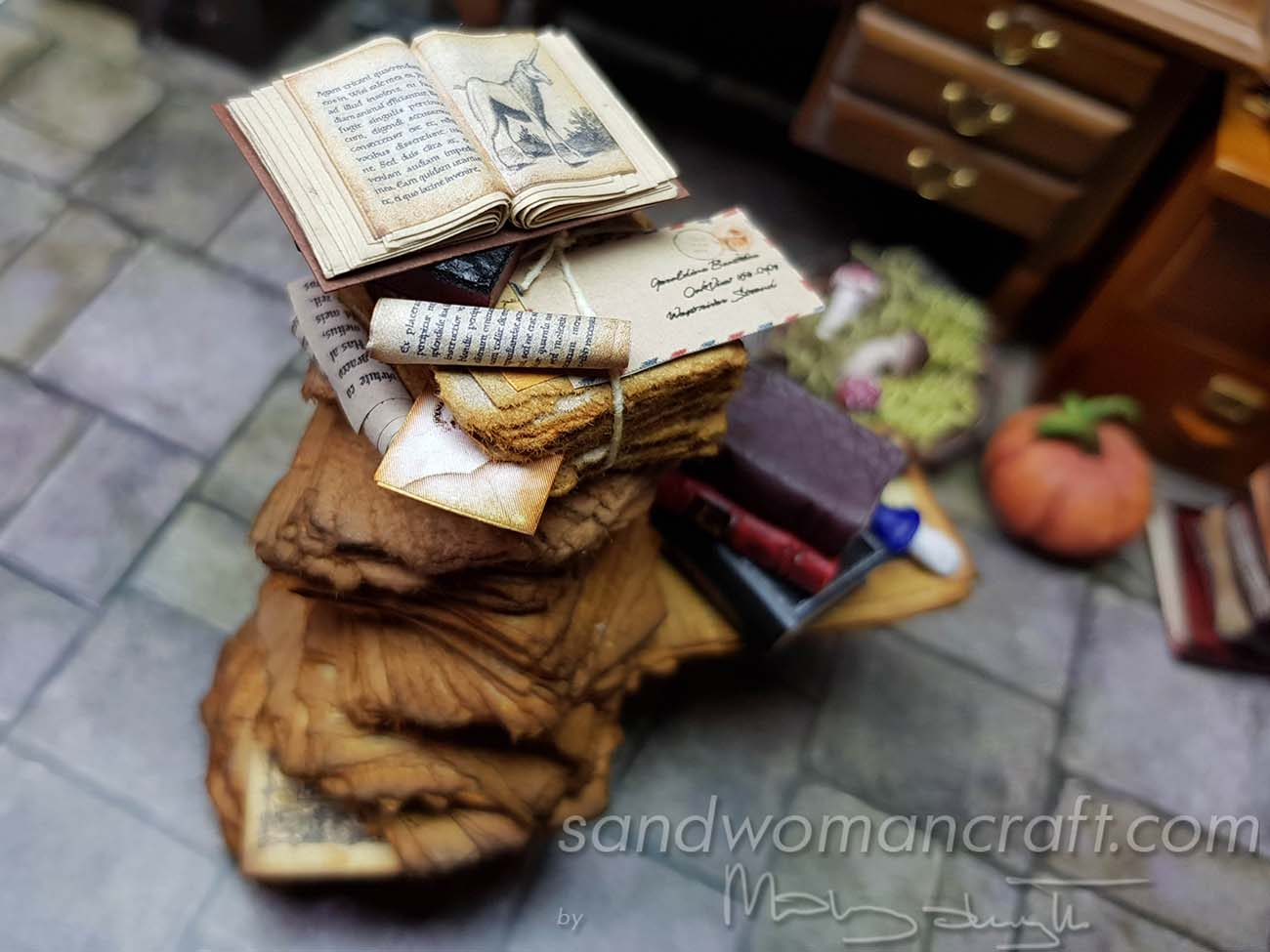 Mixed media stack with leather books, scrolls, envelopes