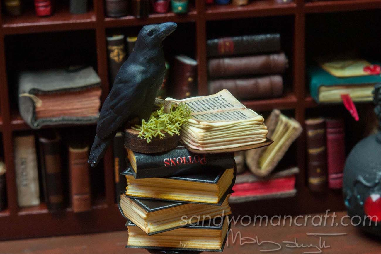 Thick miniature open book at the very top, next to the Crow