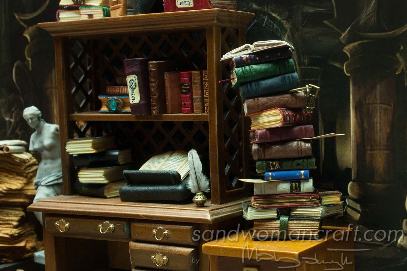 Miniature leather books stacked next to the desk