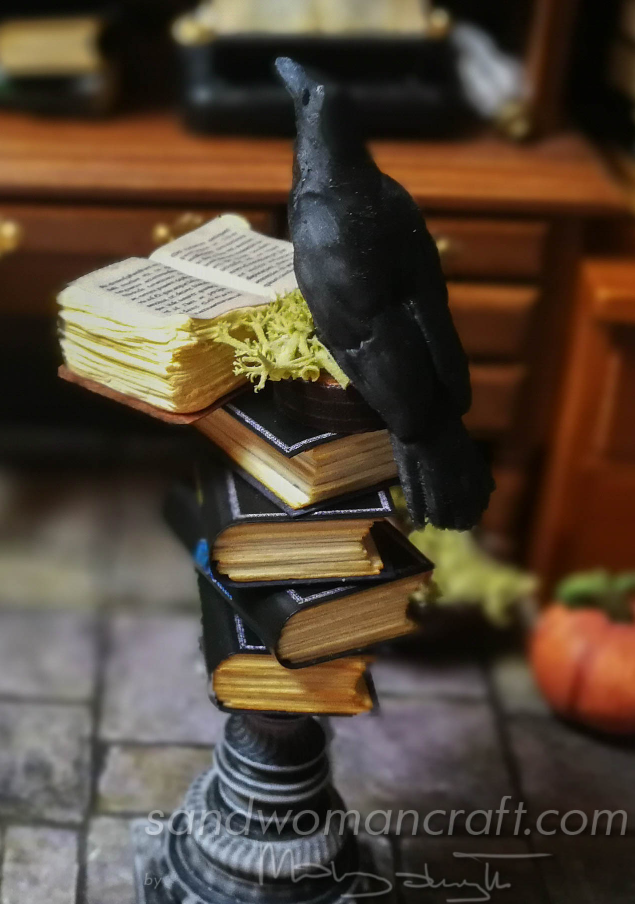 Stack of miniature books with a miniature open book and Crow at the top
