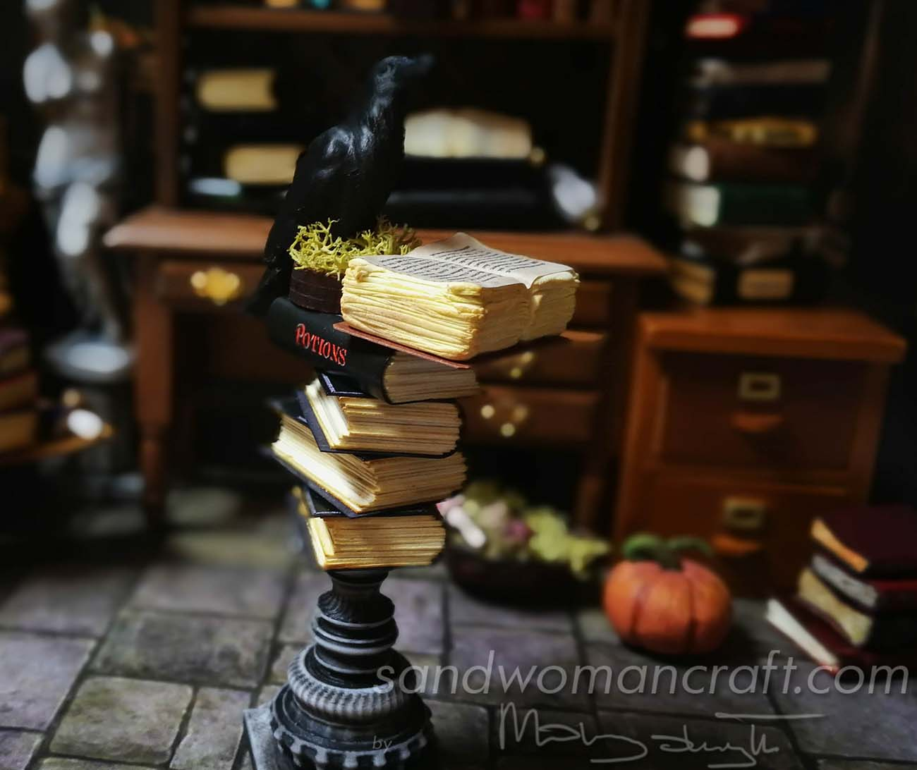 Stack of miniature books with a Crow at the top