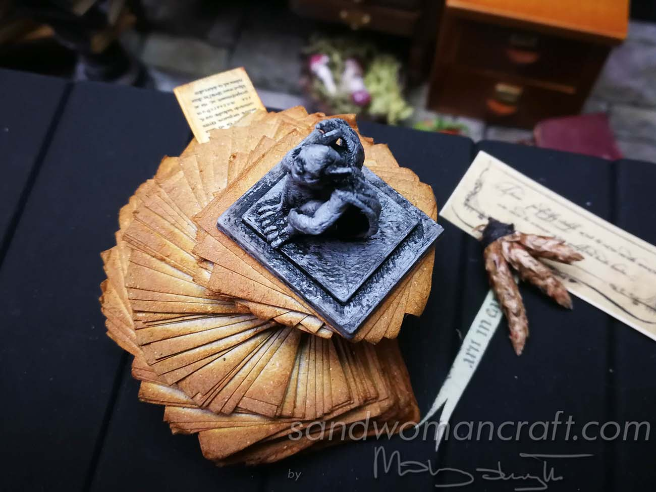 Miniature stack of aged papers with Gargoyle figurine protecting it
