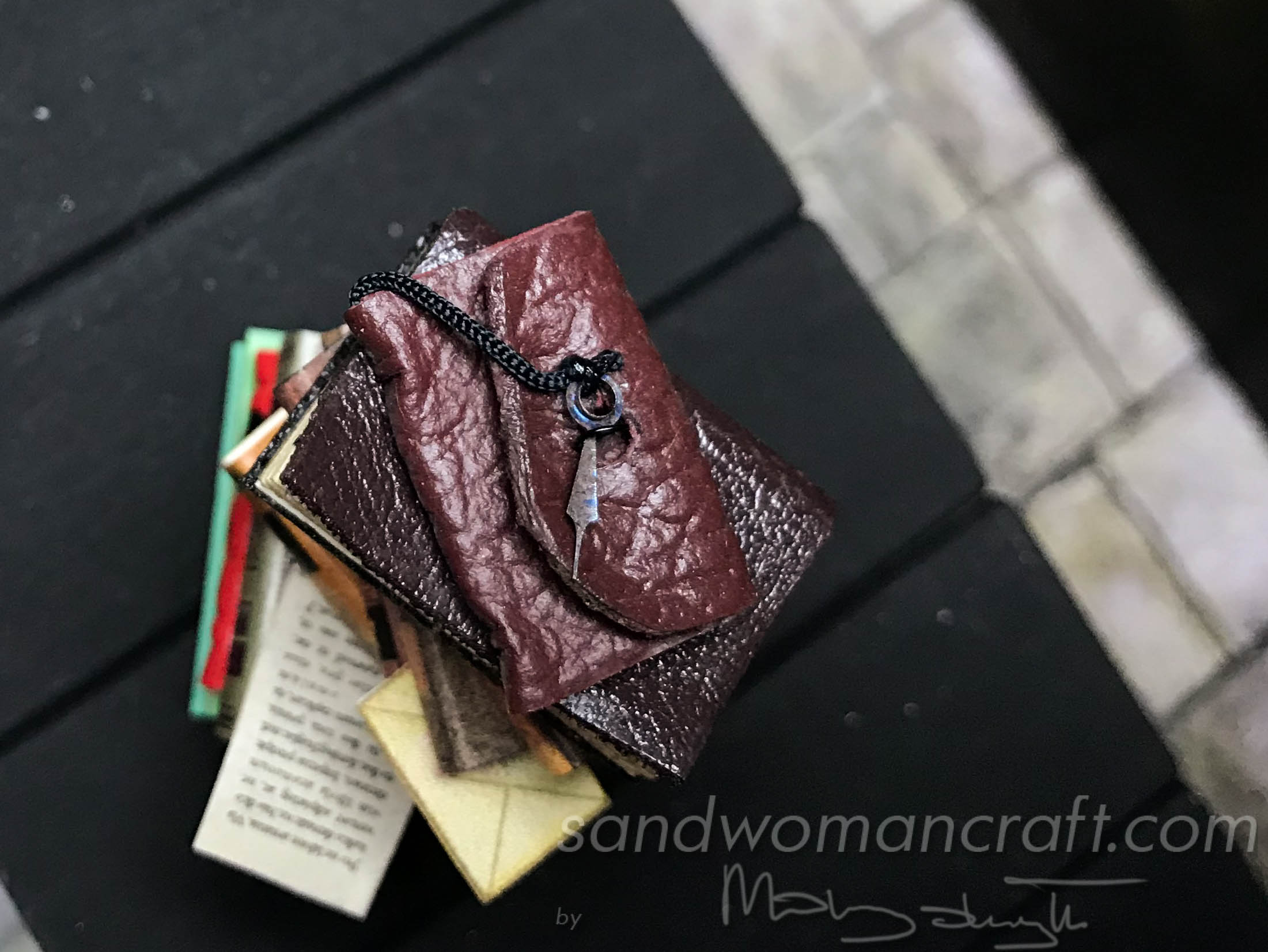 Miniature books stacked with leather art journal